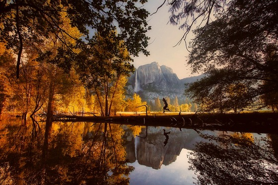 A person jumping into a lake in Yosemite National Park in autumn.