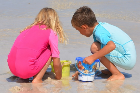 A girl and a boy playing with sand on a beach